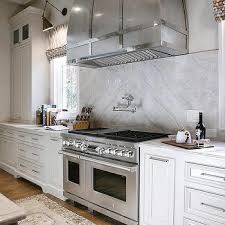 light gray kitchen cabinets with taj mahal quartzite countertops