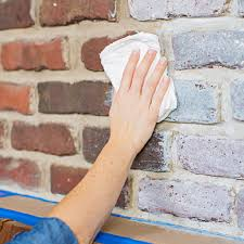 wiping paint on brick