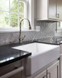 gray herringbone tiles with black quartz countertop