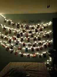 Photos clipped on a piece of string with clothes pins + Christmas lights.  solo doing