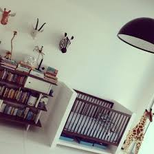 this safari themed nursery has papier mâché animals heads for wall décor and a fun large stuffed giraffe perfect for a nursery and can also work for a