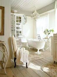 french country bathroom tranquil all white with a glass cabinet and gorgeous chandelier over the tub