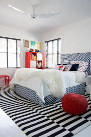 blue geometric fabric kid bed with black and white striped rug
