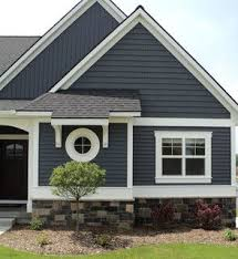 house siding colors. Dark Blue/grey Vinyl Siding On A House With Stone Veneer Around Perimeter. White Trim Black Roof The Color Is Harbour Blue, From Team Wholesale Colors
