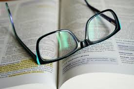 A pair of reading glasses laid on top of a textbook.