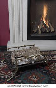 fireplaces log carrier made of brass an iron grillwork birch logs gas fire behind with composite stone surround