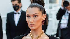 Bella Hadid covers breasts with golden ...