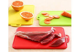 cutting board with food. Featuring Different Colors To Indicate Which Food Type They Should Be Used For - Red Raw Meat, Yellow Fruit, Green Vegetables. Cutting Board With