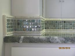bathroom 4 ceramic tub surround with border containing glass tile accents glass tile backsplash and ceramic tile floor