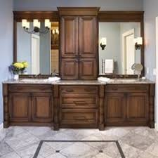 double sink vanity with center cabinet. dark stained double sink #vanity design by #ispiri. featuring dura supreme #cabinetry vanity with center cabinet s