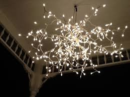 recycle on old metallic umbrella and a string of of shimmering lights for a flower chandelier easy