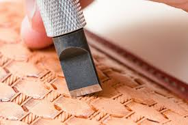 a tool being used to carve a pattern into leather