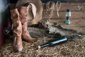 still life painting photography with traditional leather boots and american west rodeo brown felt cowboy hat