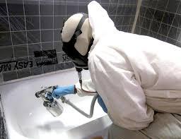 bathtub refinishing damage cost guide professional refinisher spraying a tub