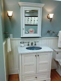 picturesque blue gray bathroom wall painted with white vinyl wainscoting also refinished white panels to gray bathroom vanity added floating mirror cabinets