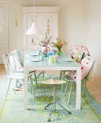 pretty shabby chic dining room with armoire and dining table with painted  chairs and area rug.