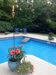 Swimming Pool Ideas : Tiki torches in the flowers around the pool
