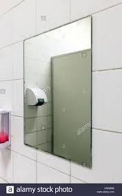 public bathroom mirror. stock photo - mirror and soap dispenser in a public bathroom h
