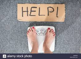 Elevated View Of Help Sign On Cardboard With Womans Feet On