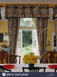 open french doors. patterned curtains at open french doors with view of garden in yellow country dining room