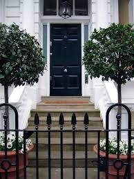 a wrought iron gate and pair of trees frame the steps toward a black panel door