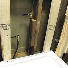 wall with backer board removed showing the wall studs and plumbing lines