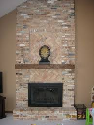 cool herringbone tile pattern and mosaic tile fireplace surround with faux wood fireplace mantel shelf
