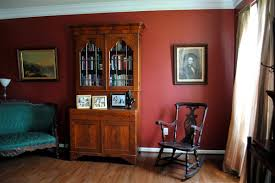 deepen the resonance of your living room with a red wall a perfect backdrop for antiques or old photographs