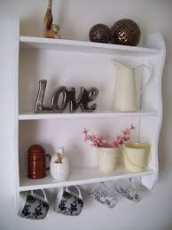 furniture white wooden wall shelves with three racks and four hooks on the wall