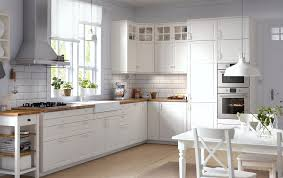 traditional kitchen with white cabinets wood worktops glass doors and integrated appliances ikea kitchen designer home visit