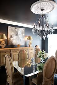 This striking black dining room mixes modern elements like the art and  mirrored table with antique