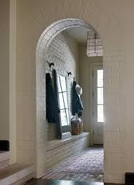 a white brick arched mudroom door way opens to red brick floor tiles covered in a red rug placed in front of a built in white brick bench topped with a full