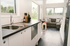 beyond the living area sits a streamlined kitchen that manages to pack in a fridge oven and dishwasher plus a cozy bathroom with a shower and a