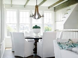 wood beams accented with a wood chandelier arteriors manning chandelier placed over a round dining table lined with white slipcovered dining chairs