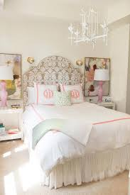 gorgeous girl s room features a white paa chandelier above a damask headboard illuminated by gold wall sconces dressed in pink hotel bedding with