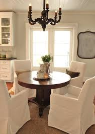 classic dining room design with ikea henriksdal slip covered armchairs seagrass rug antique french wood chandelier walnut pedestal dining table