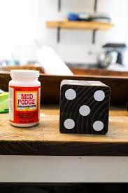wooden yard dice next to a jar of mod podge