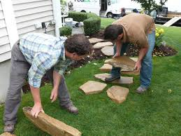 start by laying the flagstones on top of the grass to check spacing and begin to