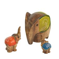 khun thanat from thailand hand carves these charming elephant figurines from reclaimed rain tree wood and meticulously finishes them with paint and fine
