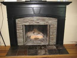 pastel colors small tile glass mosaic fireplace surround with black panted wooden fireplace mantel black granite look ceramic floor light brown teak