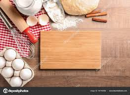 Wooden Board And Raw Dough With Ingredients On Kitchen Table