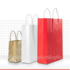 Three Paper Bags To Buy Colored With White Circles On Reflective Three paper bags to buy colored with white circles on reflective white table in a
