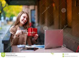 Young girl in an outdoor cafe with a laptop shows her gift through the internet
