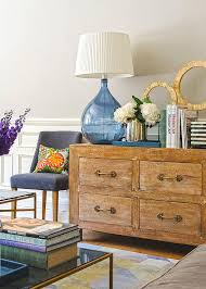 living room dresser. Amazing Living Room Boasts A Gold 4 Drawer Dresser Adorned With Hardware Topped Large Blue Glass Teardrop Lamp And Coffee Table Books Next To .