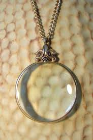 avon magnifying glass gold tone pendant