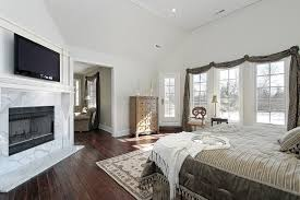 bedroom with tv. Above The Beautiful Marbled Fireplace Is A Wall Mounted Flat Screen TV, Saving Space And Bedroom With Tv P