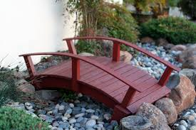 small red wooden bridge over garden with pebbles reaching pond