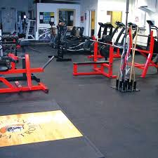 dark grey rubber home gym flooring with black pad sport equipments in white painted brick