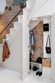 Storage Under Stairs Against Exposed Brick Wall. designs by style house  tours