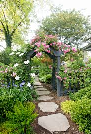 stone path in garden with gray rose trellis